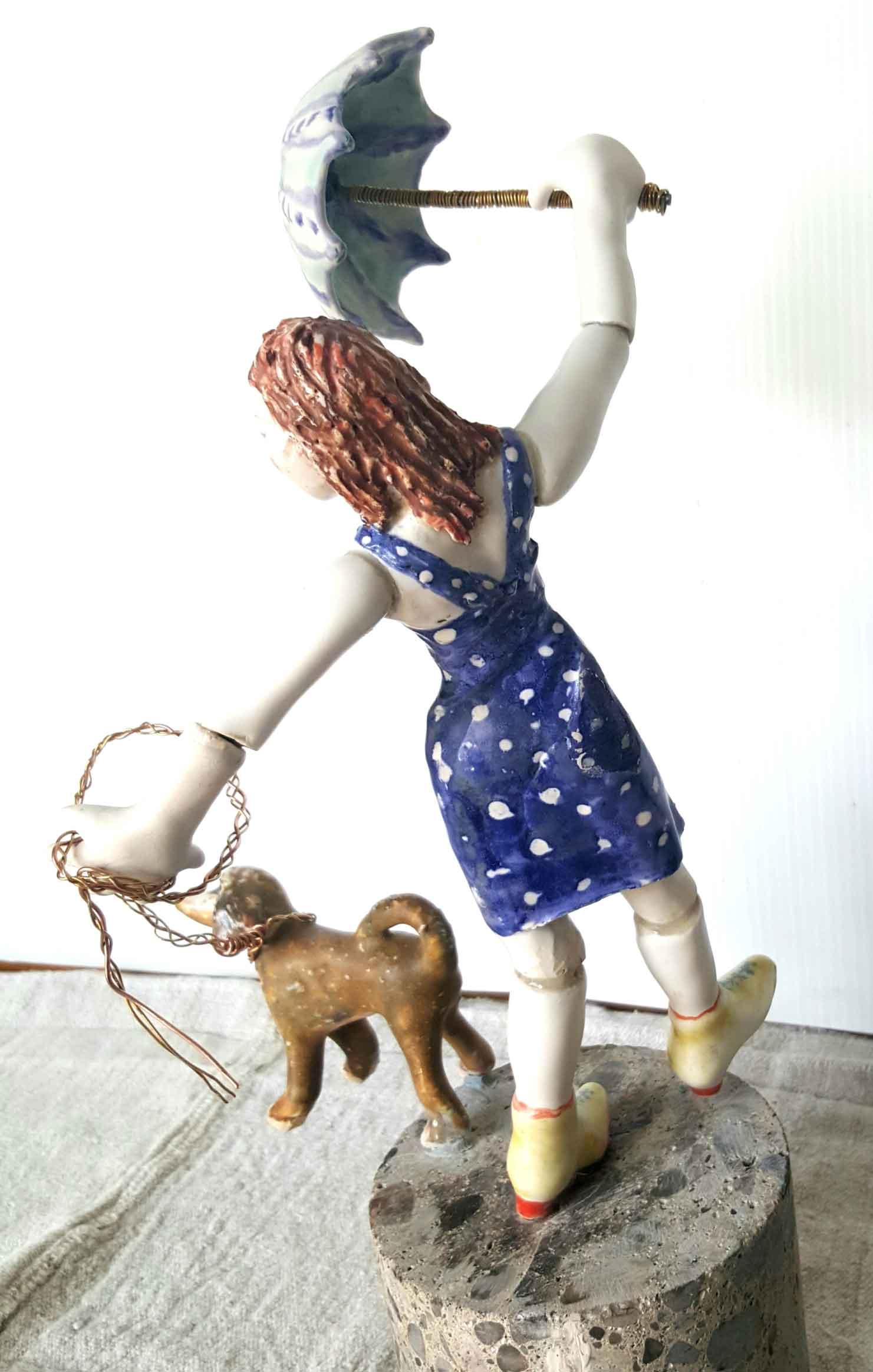 Porcelain sculpture of a woman walking a dog by Saundra Reiner