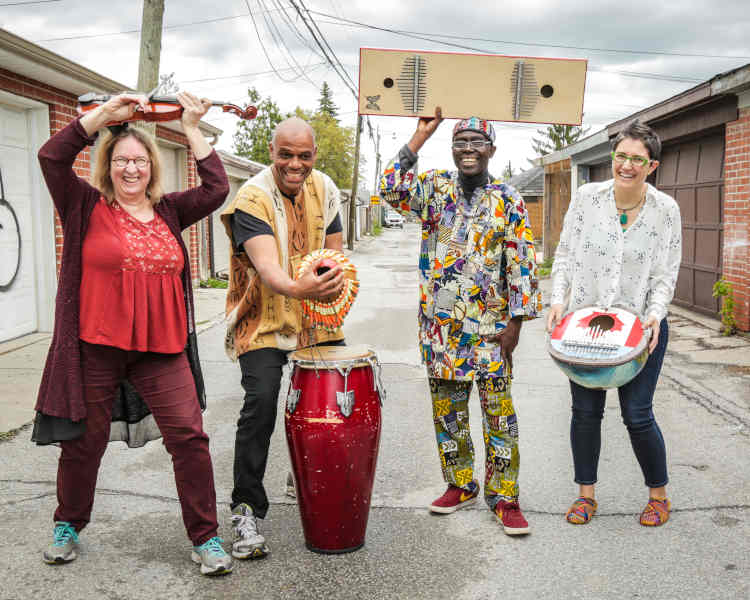 Four smiling adult musicians standing in an alleyway, each holding an instrument including kalimbas, a violin and a shekere.